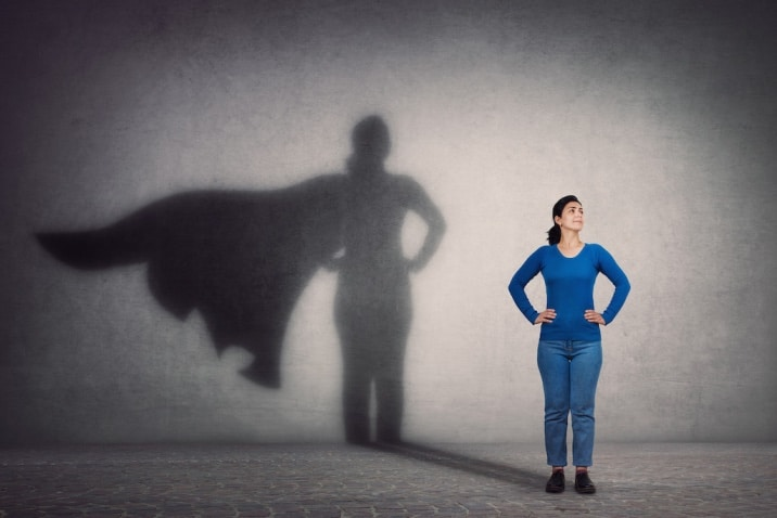 A woman standing in a power pose expressing faith in herself