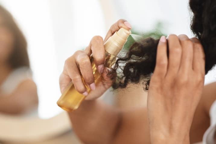 a woman applying hair spray