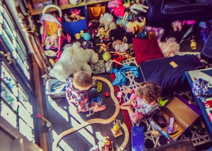 Two kids playing amidst many toys